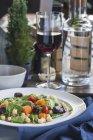 Piatto di insalata di verdure fresche e bicchiere di vino rosso — Foto stock