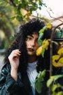 Morena muito encaracolada posando em folhas de Outono no parque. — Fotografia de Stock