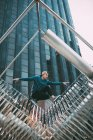 Молодой человек позирует на современной металлической скульптуре — стоковое фото