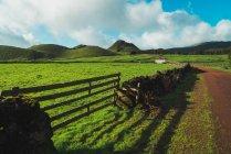 Вид на зеленое поле с забором и холмами в солнечный день . — стоковое фото