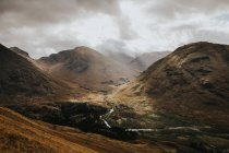Valley with small river between mountains in cloudy day. — Stock Photo