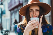 Smiling woman with cup at cafe terrace — Stock Photo