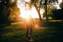 Rückansicht des hinterleuchteten Mann zu Fuß in sonnigen park — Stockfoto
