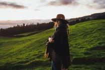 Vista laterale della donna in cappello posa sopra foschia campagna fuoco — Foto stock
