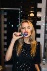 Jeune femme blonde posant avec des dents brossées et regardant la caméra . — Photo de stock