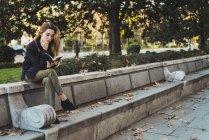 Frau sitzt auf einer Steinbank zurück und Lesebuch im park — Stockfoto