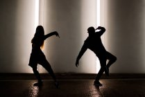 Silhouette of couple dancing on street — Stock Photo