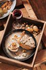 Various appetizers in a tray with cheese, bread and wine — Stock Photo