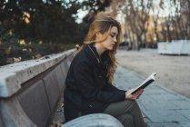 Vue latérale du livre de lecture de femme sur le banc dans le parc — Photo de stock