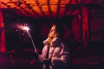Woman posing with purple smoking torch in abandoned building — Stock Photo