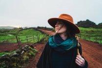 Donna in cappello a piedi sulla strada rurale di campagna — Foto stock