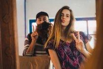 Junger Mann nehmen Selfie mit Frau gestikulieren zwei Finger am Spiegel — Stockfoto