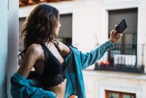 Young woman taking selfie with smartphone on balcony — Stock Photo