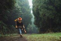 Vista posteriore della donna che cammina con ukulele nella strada forestale rurale — Foto stock