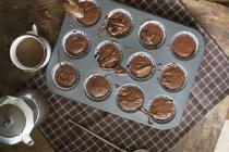 De arriba vista de magdalenas de chocolate crudo en bandeja para hornear preparada para hornear en la mesa . - foto de stock