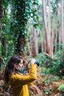 Вид збоку молодий фотограф жінка, стоячи в лісі і прийняття знімків з камери. — стокове фото