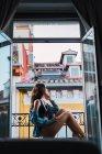 Женщина в черном белье сидит на подоконнике — стоковое фото