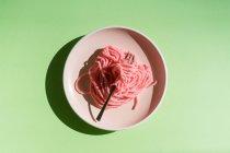 Vista dall'alto di vermi gelatina rosa disposti su piatto con forchetta su sfondo verde — Foto stock