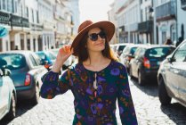 Cheerful stylish woman in hat walking on sunlit streets — Stock Photo