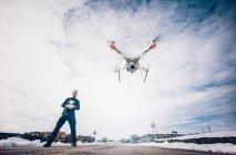 Homem drone voador com controle remoto sobre paisagem nebulosa cênica — Fotografia de Stock