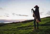 Vue latérale de la femme prenant des photos avec caméra dans les champs verts — Photo de stock