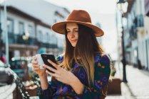 Femme au chapeau assis à la terrasse du café avec coupe et smartphone — Photo de stock