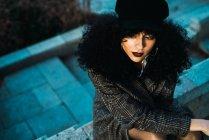 Молодая брюнетка кудрявая женщина в пальто позирует на заборе у лестницы в городском парке . — стоковое фото