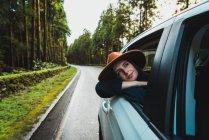 Молодая женщина в шляпе из окна автомобиля, опираясь на лесной дороге — стоковое фото