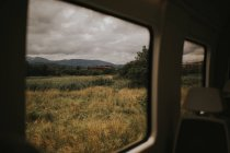 View to dry meadow in cloudy day seen from car — Stock Photo