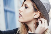 Portrait of young blonde woman listening music with earphones — Stock Photo