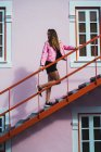 Young woman in pink coat posing on stairs on street — Stock Photo