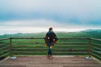 Giovane donna in piedi sulla terrazza con vista estesa delle terre verdi sotto le nuvole . — Foto stock