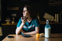 Charming woman having breakfast and looking aside — Stock Photo
