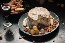 Натюрморт плиты с голубым сыром и виноград, грецкие орехи на темной таблицы — стоковое фото