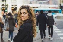 Donna che osserva sopra la spalla alla macchina fotografica su strada — Foto stock