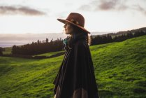 Vista laterale della donna in elegante cappello in piedi su sfondo di praterie verdi e nuvole . — Foto stock