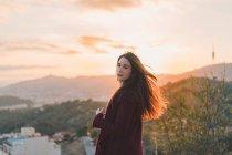 Femme souriante posant sur la colline du soir — Photo de stock