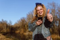 Cheerful young woman with smartphone gesturing thumb up — Stock Photo