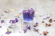 Verre de thé Papillon Pois infusé aux pétales tendres sur table en bois . — Photo de stock