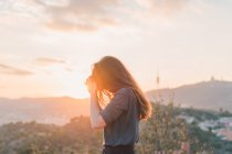 Side view of young woman posing on hill in sunset light — Stock Photo