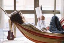 Вид сбоку женщины в гамаке, расслабляющейся с книгой — стоковое фото