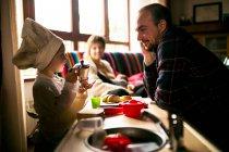 Отец, глядя на сына в шеф-повар форма дома — стоковое фото
