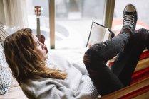 Женщина лежит в гамаке расслабляясь с книгой — стоковое фото