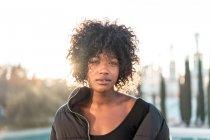 Stylish curly woman looking at camera — Stock Photo