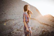 Tender brunette girl in summer dress posing on rocky terrain — Stock Photo
