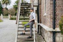 Hombre pensativo en gorra posando en escaleras - foto de stock
