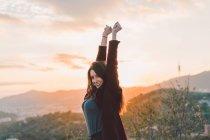Усміхаючись жінка розтяжку руки на пагорбі у вечорі — стокове фото