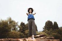 Sinnliche Brünette Frau posiert mit Hut auf Protokoll-Stapel — Stockfoto