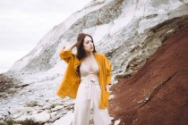 Brunette girl in bra and yellow jacket posing at coastline — Stock Photo