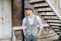 Человек в винтажной одежде позирует у лестницы — стоковое фото